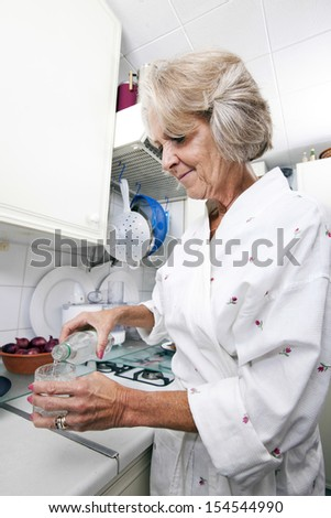 Senior woman pouring water in glass while standing at kitchen counter