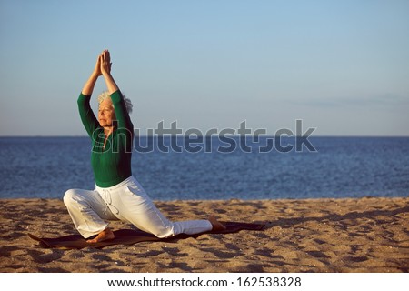Senior woman practicing yoga on beach. Elderly woman doing yoga exercise on sandy beach. Yoga and relaxation concept.