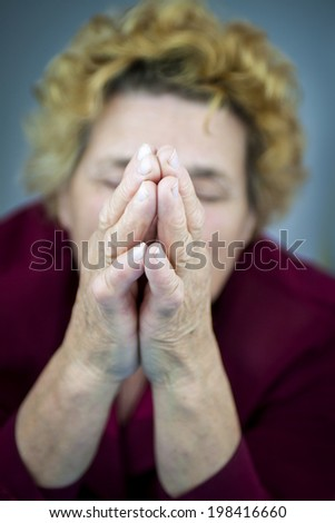 Senior woman praying. Blurred background