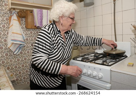 Senior woman prepares food on the gas stove in her kitchen. She takes cover of the frying pan. - stock photo