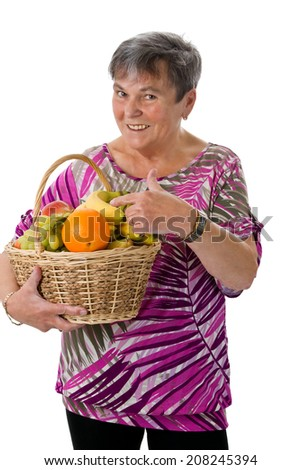 Senior woman presenting a basket of fruit - isolated - stock photo