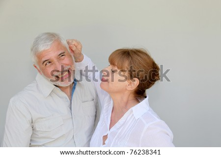 Senior woman pulling on husband's ear - stock photo