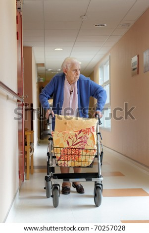 senior woman pushing a walking frame in a  retirement facility - stock photo