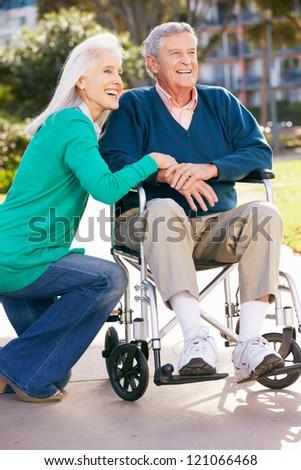 Senior Woman Pushing Husband In Wheelchair - stock photo