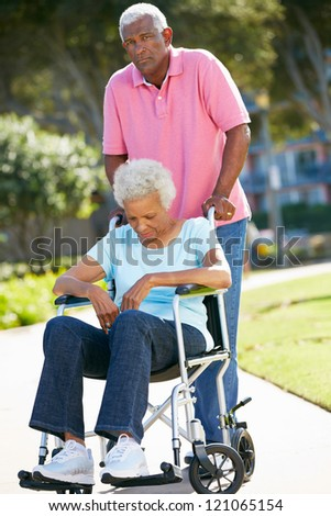 Senior Woman Pushing Unhappy Husband In Wheelchair - stock photo