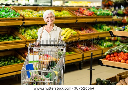 Senior woman putting banana in her trolley in supermarket