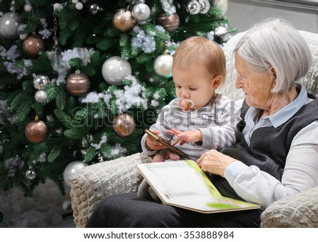 Senior woman reading a book to her baby grandson beside a Christmas tree, the boy is playing with a smartphone - stock photo