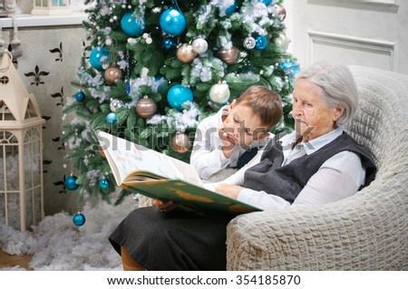 Senior woman reading a book to her grandson beside a Christmas tree - stock photo