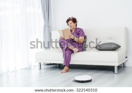Senior woman reading a book while robot vacuum cleaning floor at home. Modern lifestyle concept.