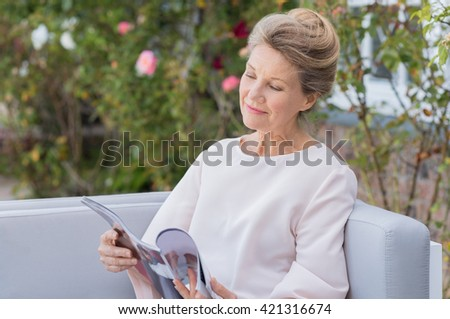 Senior woman reading a magazine sitting on a couch outdoor. Happy elderly woman reading a gossip magazine in her free time. Mature woman relaxing in the garden. - stock photo