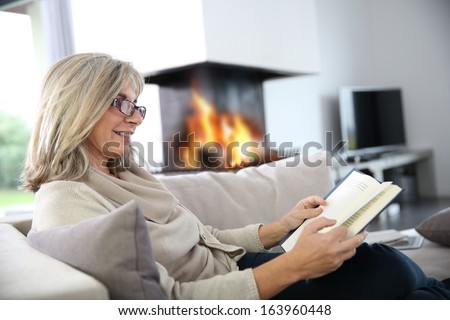 Senior woman reading book at home by fireplace - stock photo