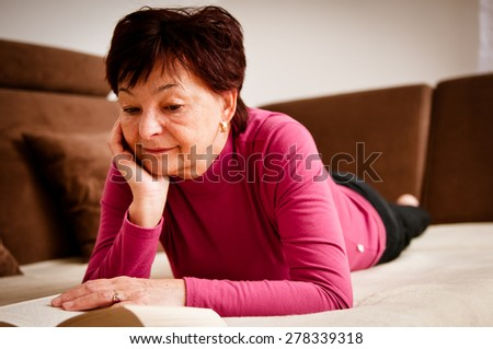 Senior woman reading book at home on sofa - stock photo