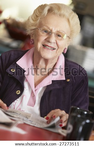 Senior woman reading newspaper - stock photo