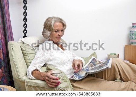 Woman Reading Newspaper At Home