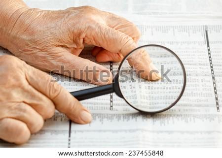 Senior woman reading stock listings - stock photo