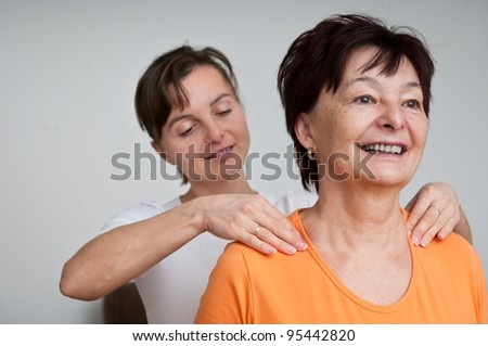 Senior woman receives neck massage from young person - stock photo