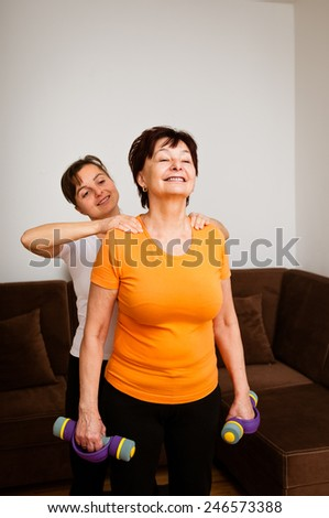 Senior woman receives shoulder massage during exercise - stock photo