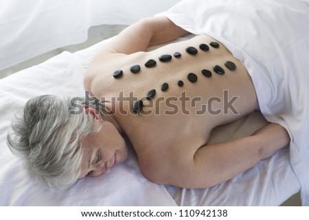 Senior woman receiving hot stone massage - stock photo