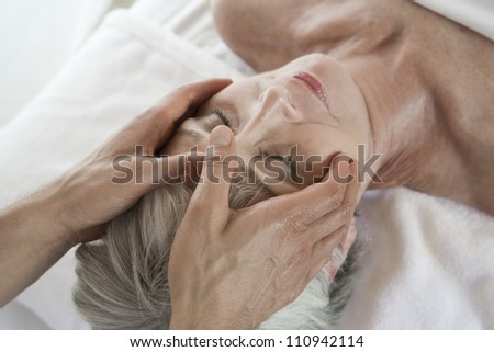 Senior woman receiving neck massage at spa - stock photo