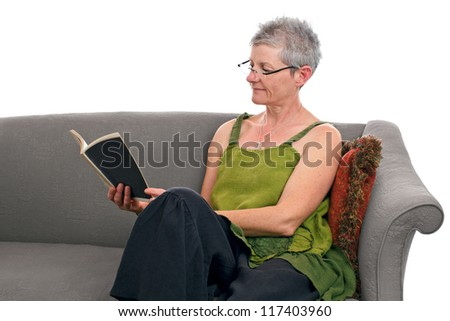 Senior woman relaxes seated on gray sofa and reads a paperback book. She has short gray hair and wears a loose green and black linen dress. Horizontal, isolated on white background, copy space.