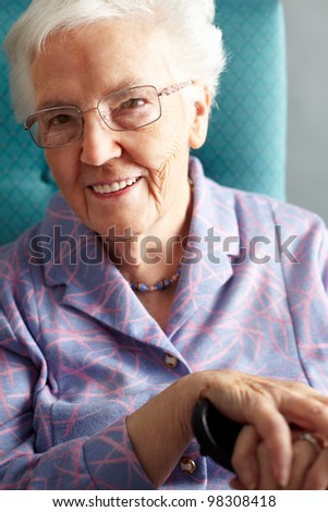 Senior Woman Relaxing In Chair Holding Walking Stick - stock photo