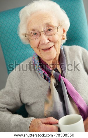 Senior Woman Relaxing In Chair With Hot Drink - stock photo