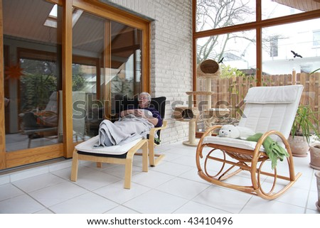 senior woman relaxing in conservatory - stock photo