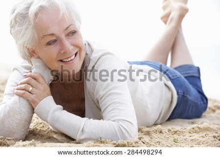 Senior Woman Relaxing On Beach - stock photo