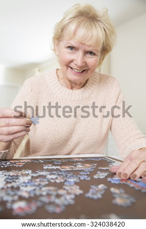 Senior Woman Relaxing With Jigsaw Puzzle At Home - stock photo