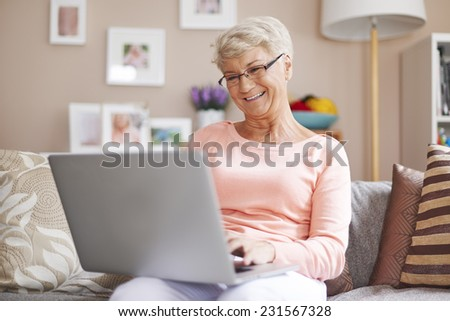 Senior woman relaxing with laptop on sofa  - stock photo