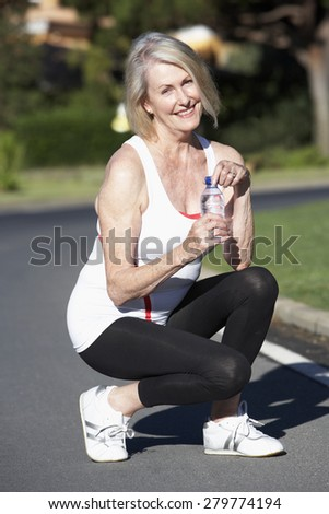 Senior Woman Resting And Drinking Water After Exercise - stock photo