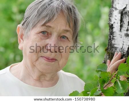 Senior woman's portrait in summer. Selective focus - stock photo