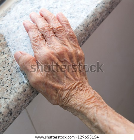 Senior woman's wrinkled hand near the window. - stock photo
