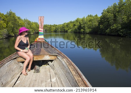 Senior woman sat in the prow of a boat meandering through mangroves in Trang Province, Thailand - stock photo