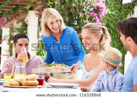 Senior Woman Serving At Multi Generation Family Meal - stock photo