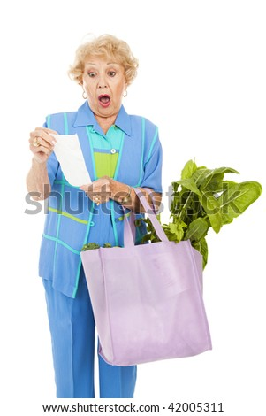 Senior woman shocked by the price of groceries.  Isolated on white. - stock photo