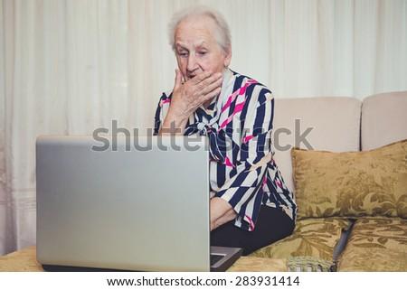 Senior woman shocked with something on laptop screen - stock photo