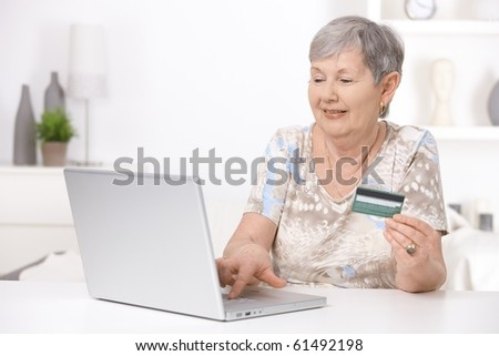 Senior woman shopping on internet, paying with credit card.?