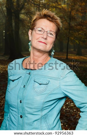 Senior woman short blond hair wearing glasses and blue jacket standing in autumn forest