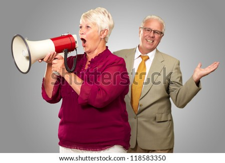 Senior Woman Shouting In Megaphone In Front Of Businessman On Gray Background - stock photo