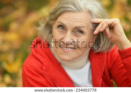 Senior woman showing thumbs up in the park in autumn - stock photo