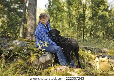 Senior woman sits on a rock in the forest. A curly haired retriever beside her looks at the camera. There's a rucksack and binoculars at the side of the picture