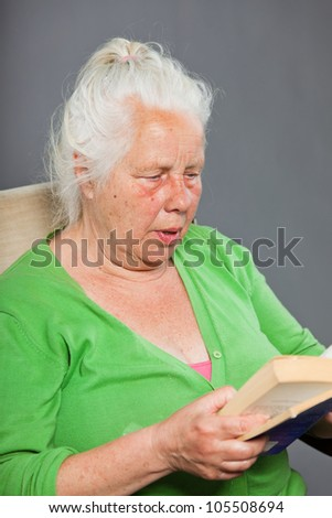 Senior woman sitting chair reading a book. Grey long hair. Studio shot isolated on grey background.