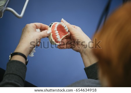 Senior Woman Sitting In A Chair Looking At The Dentures