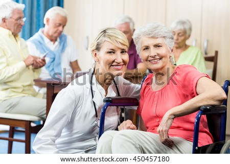 Senior woman sitting in a wheelchair in a retirement home - stock photo