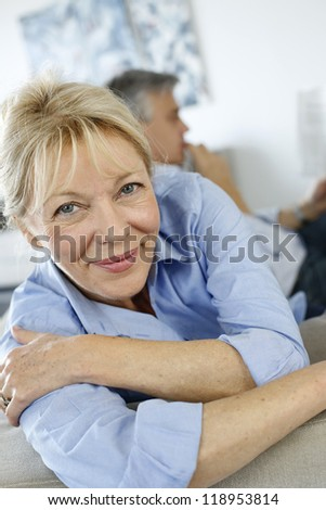 Senior woman sitting in couch, husband in background - stock photo