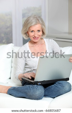 Senior woman sitting in sofa with laptop computer