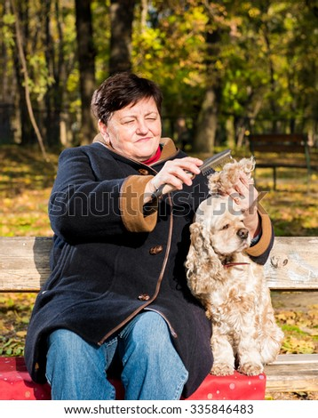 Senior woman sitting on a bench with a dog in autumn park