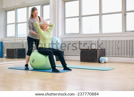 Senior woman sitting on a pilates ball  exercising at health club being assisted by her personal trainer. Physical therapist helping senior woman in her workout at gym. - stock photo