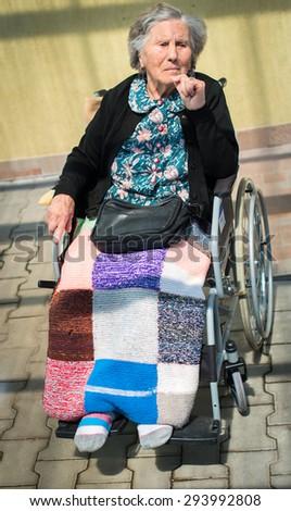 senior woman sitting on a wheelchair outdoors - stock photo